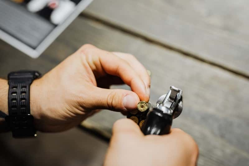 Person holding centerfire bullet by gun